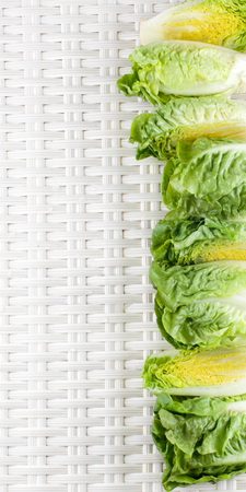 romaine lettuce: Frame of Fresh Crunchy Romaine Lettuce Full Heads and Halves with Water Drops closeup on Wicker background Stock Photo