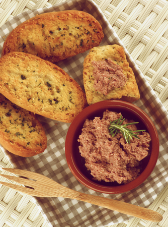 retro styled: Delicious Homemade Meat Pate with Crispy Herbs Bread in Checkered Tray with Wooden Fork closeup on Wicker background. Retro Styled