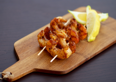 prepared shellfish: Delicious Grilled Prawns on Wooden Sticks with Sliced Lemon closeup on Wooden Cutting Board. Focus on Foreground