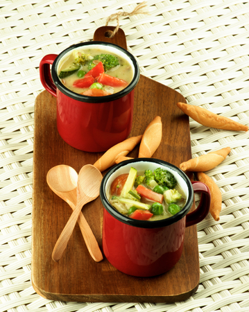 green pea: Delicious Homemade Vegetables Creamy Soup with Broccoli, Carrots, Zucchini, Leek, Red Bell Pepper and Green Pea in Red Soup Cups with Wooden Spoon and Bread Sticks closeup Wicker background