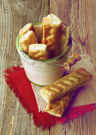 danish puff pastry: Puff Pastry Sticks Sprinkled with Sugar Crystals in White Bucket on Napkins closeup on Wooden background. Retro Styled