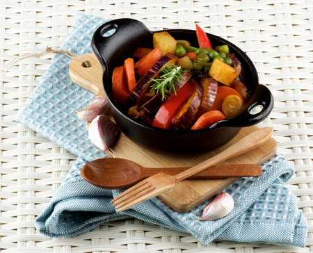 green pea: Delicious Homemade Colorful Vegetables Ragout with Striped Eggplant, Carrots, Potatoes, Red Bell Pepper and Green Pea in Black Iron Stewpot with Wooden Fork and Spoon closeup Blue Napkin on Wicker background