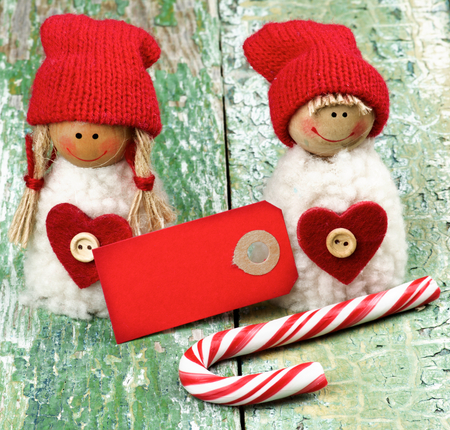 Christmas Decoration Concept with Handmade Dolls in Knit Hats, Striped Sweet Cane and Greeting Card closeup on Rustic Cracked background Stock Photo