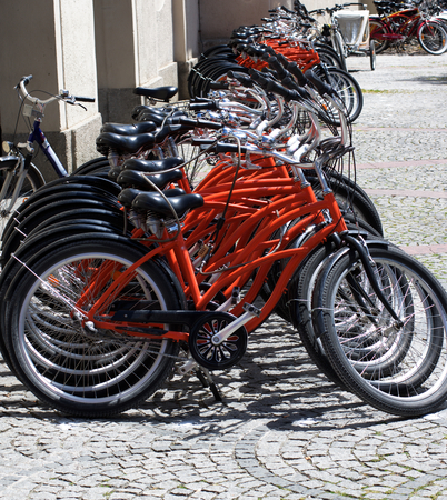 Arrangement of Parked Rental Bicycles on Paving Stone Sidewalk in Summer Day in Europe Outdoors Stock Photo