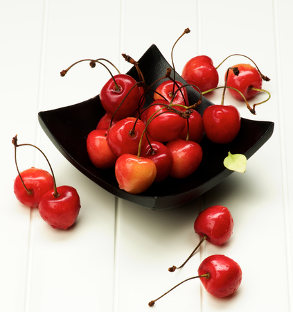 bing: Ripe Sweet Maraschino Cherries in Black Wooden Plate closeup on White Plank  background