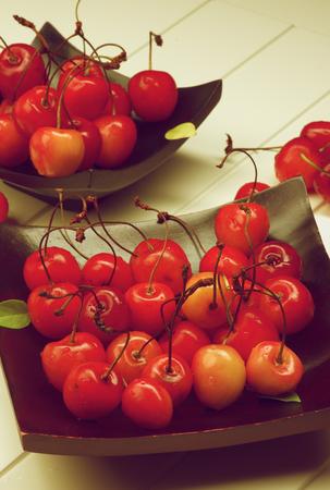 retro styled: Fresh Ripe Sweet Maraschino Cherries on Black Wooden Plates closeup on Plank White background. Retro Styled