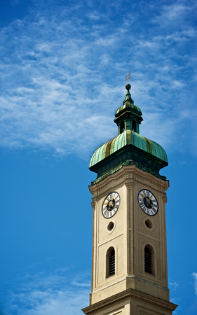 Clock Tower Heilig Geist Kirche against Blue Cloudy Sky Outdoors. Munich, Germany Stock Photo