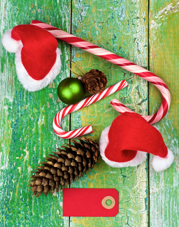 cordon tape: Christmas Decoration Concept with Small Santa Hats, Striped Sweet Cane, Fir Cones and Greeting Card closeup on Rustic Cracked background