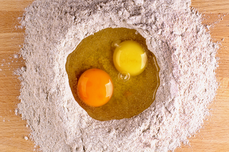 doughy: Two Light Yellow and Dark Yellow Egg Yolks into Heap of Whole Wheat Flour closeup on Wooden Table