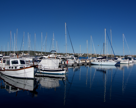 boat crew: Various Anchor Yachts with Reflection in Surface of Sea in Marina of Mahon, Menorca, Spain