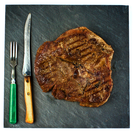 shank: Delicious Grilled Steak Beef Shank on Black Stone Plate with Retro Fork and Knife Cross Section on White background