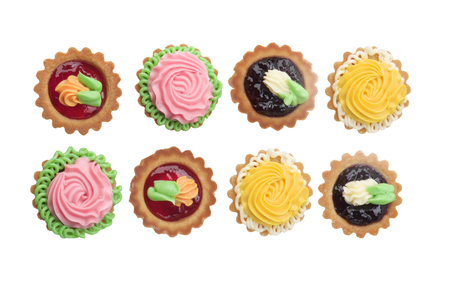 Arrangement of Delicious Little Tarts with Colored Butter Cream, Fruit Jam and Decoration In a Rows isolated on White background. Top View
