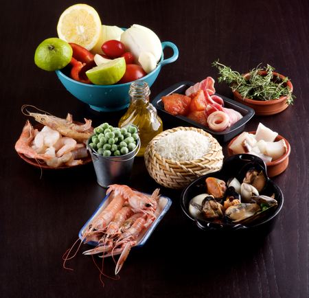 Raw Ingredients of Spanish Traditional Paella with Various Seafood, Mussels, Vegetables, Rice, Green Pea and Olive Oil closeup on Dark Wooden background