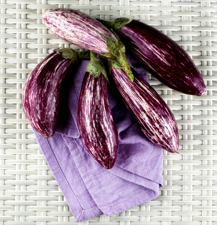 variegated: Stack of Fresh Raw Striped Eggplants on Purple Napkin closeup on Wicker background