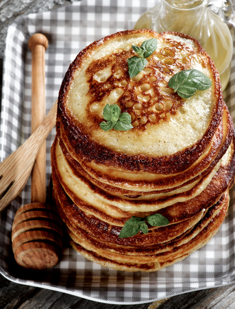 Stack of Homemade Pancakes with Mint Leafs, Honey, Wooden Fork and Honey Dipper closeup in Checkered Tray