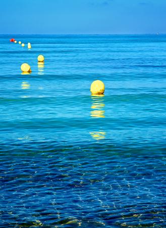 Gele grens Mark drijft op rimpel zeewater oppervlaktewater op Blue Sky Horizon buitenshuis