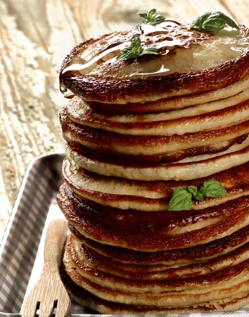 Stack of Delicious Homemade  Pancakes with Honey  and Mint Leafs on Checkered Tray closeup on Wooden background
