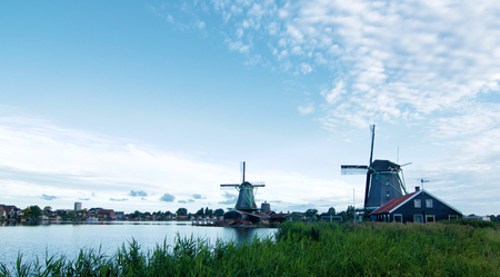 Famous Zaanse Schans Windmills from River Coast with Green Grass Early Morning Outdoors