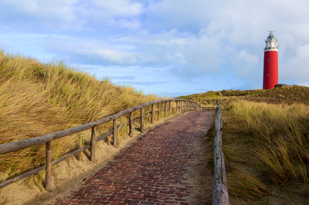 Brick Road to Lighthouse Texel on Blue Cloudy Sky background Outdoors. National Park Duinen van Texel, Texel Island, Netherlands Imagens - 99454716