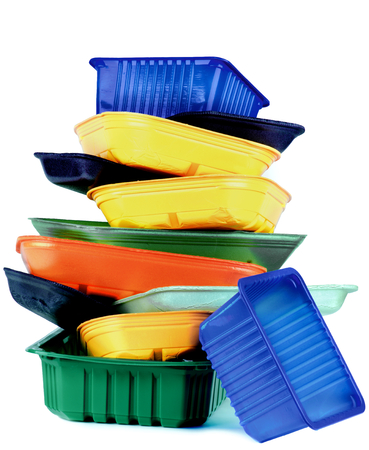 Stack of Various Colored Empty Plastic Recycled Trays isolated on White background