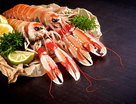 Two Big Delicious Raw Langoustines with Rosemary, Lemon and Lime on Parchment Paper closeup on Dark Wooden background Stock Photo