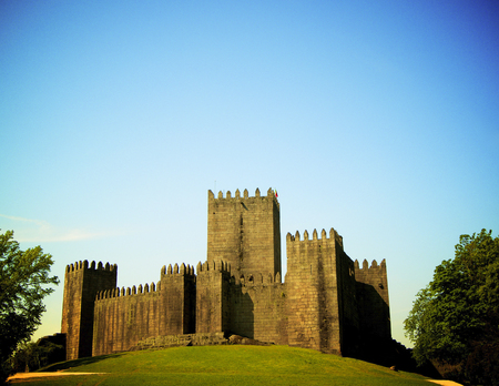 Famous Medieval Portuguese Guimaraes Castle against Blue Sky in Sunny Day Outdoors