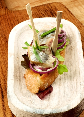 Delicious Fish Tapas with Marinated Sardines, Red Onion and Greens closeup on White Wooden Plate on Wooden background