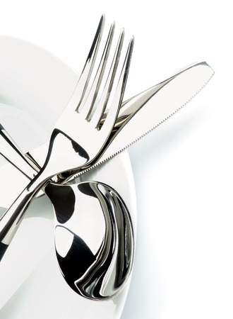 Arrangement of Silverware with Fork, Table Knife and Soup Spoon on White Plate closeup on White background