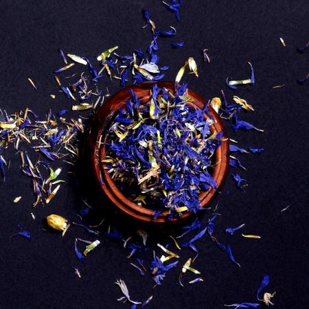 Arrangement of Tea Leafs with Cornflowers in Wooden Jar closeup on Black background. Top View Standard-Bild - 124962691