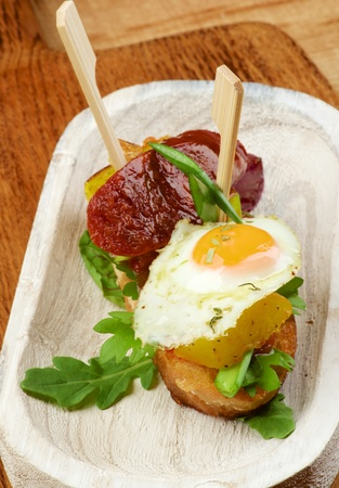 Delicious Spanish Tapas with Fried Quail Egg, Roasted Chorizo and Potato with Green Onion on Baguette Bread closeup on Wooden background