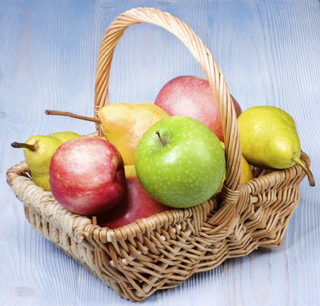Arrangement of Various Colorful Ripe Apples and Pears in Wicker Basket closeup on Blue Wooden background Standard-Bild - 124962695