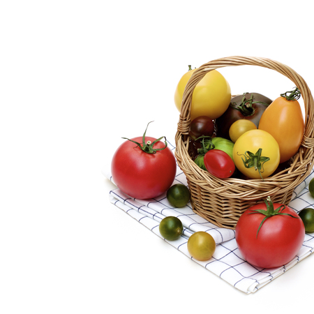 Fresh Organic Colorful Tomatoes in Wicker Basket on Checkered Napkin Cross Section on White background Standard-Bild - 124962733