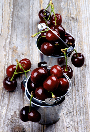 Dark Red Sweet Cherries in Tin Buckets Full of closeup on Rustic Wooden background Standard-Bild - 124963042