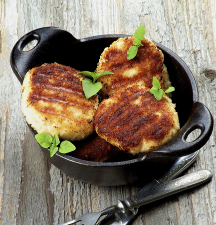 Delicious Homemade Fried Meat Cutlets in Black Saucepan closeup on Rustic Wooden background Standard-Bild - 124963138