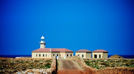 Punta Nati Lighthouse against Blue Sky Outdoors. Menorca, Balearic Islands Standard-Bild - 124963171