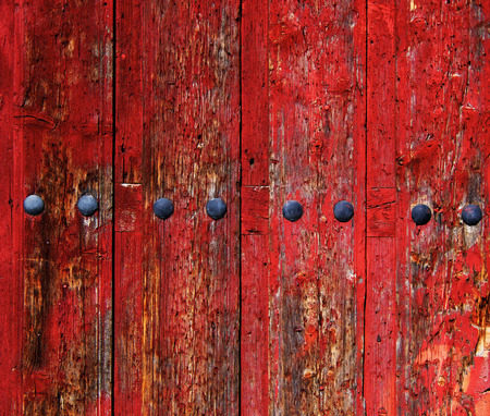 Old Red Cracked Wooden Background with Rivets In a Row closeup Outdoors Standard-Bild - 124963174