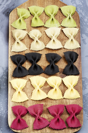 Raw Five Colors Farfalle Pasta closeup on Wooden Cutting Board on Grey background Imagens