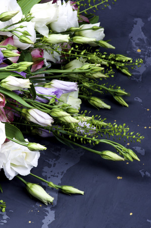 Corner Frame of Elegant White and Lilac Lisianthus and Decorative Green Stems closeup on Grey Grunge background