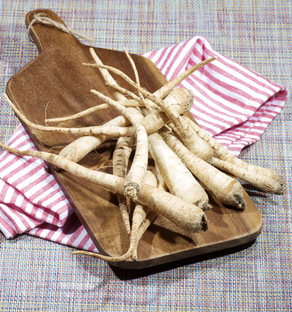 Heap of Fresh Ripe Parsnip Roots on Wooden Cutting Board closeup on Striped Napkin