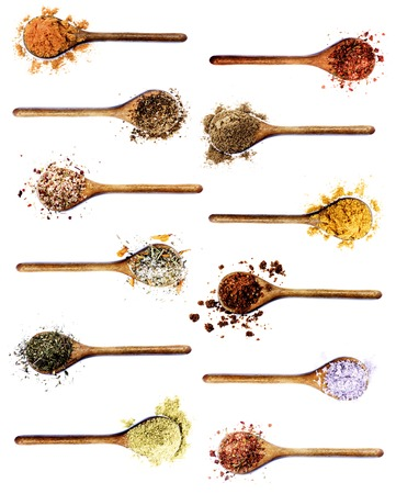 Collection of Spices in Wooden Spoons: Curry, Coriander,  Dried Paprika, Salt with Chili and Petals, Thyme, Cumin and Turmeric, Dried Chili and Kosher Salt isolated on White background