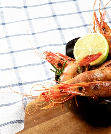 Delicious Roasted Shrimps in Black Cast Iron with Lime on Wooden Cutting Board closeup on Checkered Napkin background