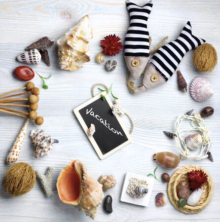 Summer Vacations Concept with Handmade Decorations, Various Shells, Dry Plants  and Chalk Board with Inscription Vacation closeup on Light Blue Wooden background Standard-Bild - 124963606