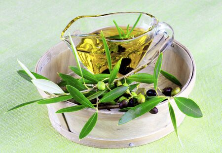 Glass Gravy with Olive Oil, Raw Green and Black Olives with Leafs in Wooden Bowl closeup on Green Textile background Standard-Bild - 124963611