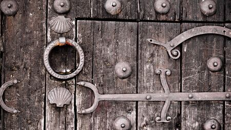 Ancient Wooden Door with Forged Metal Elements, Braces and Hinge closeup Outdoors Standard-Bild - 124963613