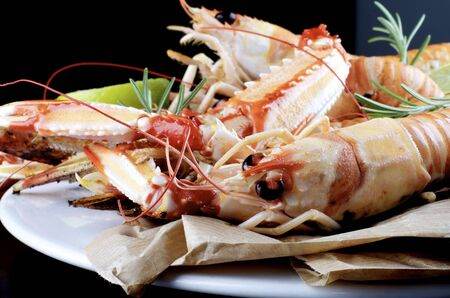 Delicious Grilled Langoustines with Rosemary on Parchment Paper and White Plate closeup on Dark Wooden background Standard-Bild - 124963855
