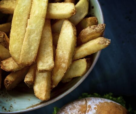 Delicious Homemade French Fries in Blue Bowl closeup Outdoors