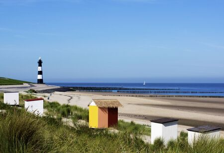 Breskens Lighthouse and Landscape on Coast of North Sea against Blue Sky background Outdoors. Zeeland, Netherlands