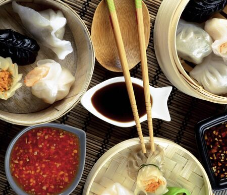Arrangement of Various Dim Sum in Bamboo Steamed Bowls, Chili and Soy Sauces and Chopsticks closeup on Straw Mat background. Top View