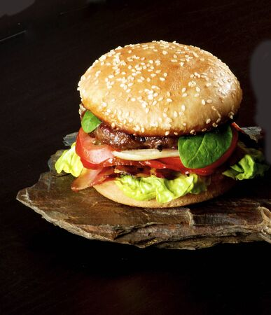 Fresh Tasty Hamburger with Beef, Bacon, Lettuce, Tomatoes, Basil, Roasted Onion and Juicy Sauce into Sesame Bun on Stone Board closeup on Dark background