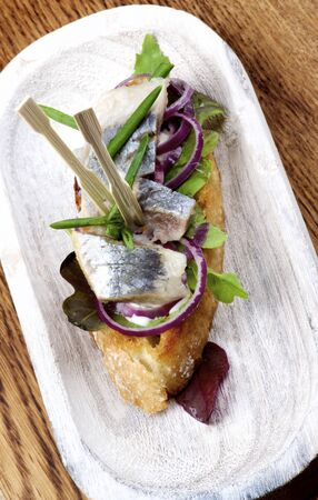 Delicious Spanish Tapas with Marinated Sardines, Red Onion and Greens closeup on Wooden Plate. Top View